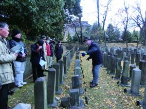 西南戦争戦病死者墓碑の前で説明される吉岡氏